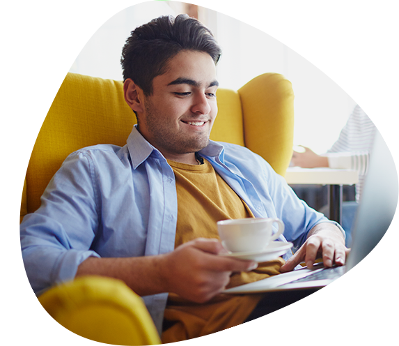 Man Relaxing in Armchair With Cup of Tea Using Laptop Computer